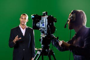 A television presenter in a TV studio with a camera and operator out of focus in the foreground and a green screen in the background. Some motion blur on the presenter's head and hands.
